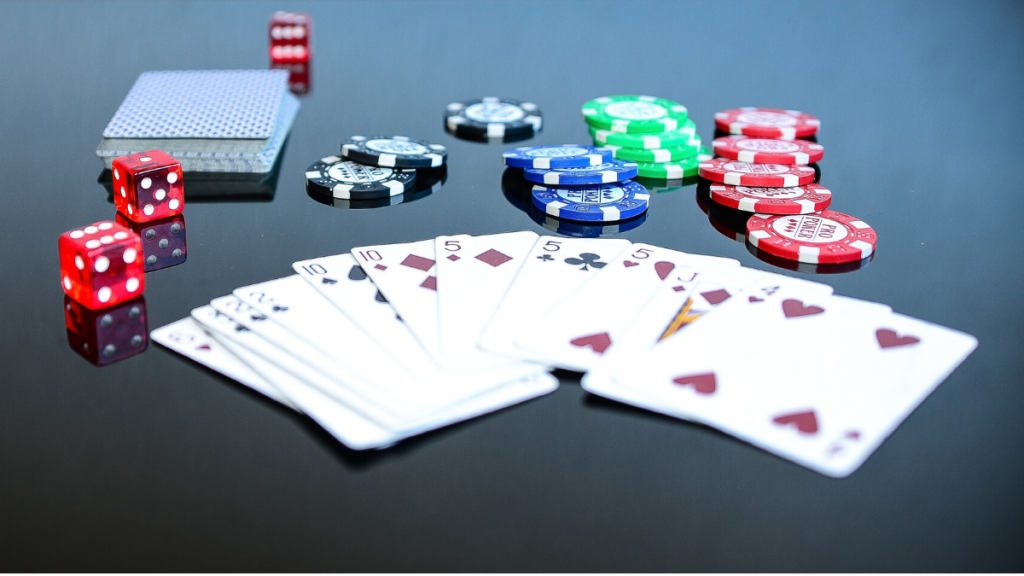 A picture of fanned out cards withpoker chips and dice behind them