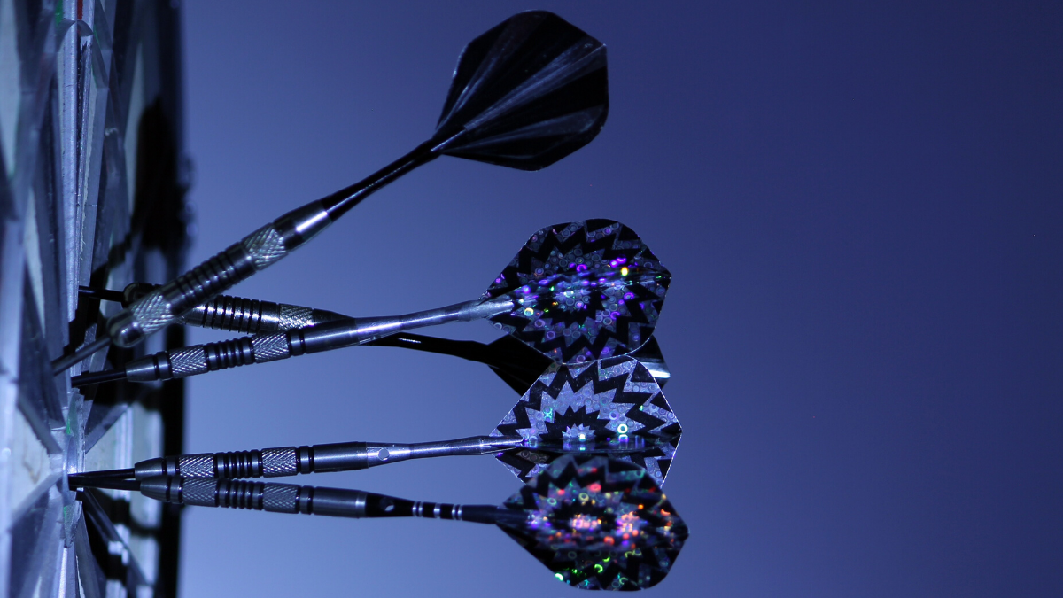 A picture of a dartboard with darts in it in an artistic blue light and from a side view.