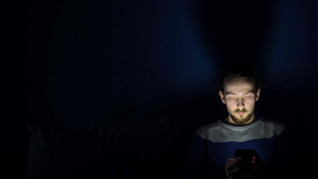 A picture of a man sat alone with a screen in front of him - he's addicted.