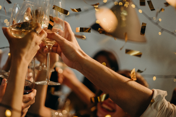 Picture of people celebrating with champagne to represent being happy that the betting shops reopen - you can only see their arms and glasses. They aren't socially distancing, whoops.