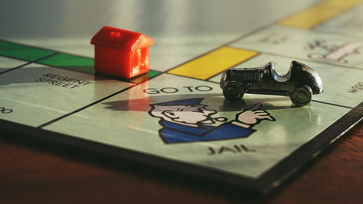 A picture of a monopoly board (just the corner) with a house on it to represent taking advantage and the house.