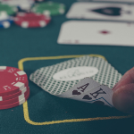 Picture of a poker game with someone's hand peeking at the cards. To represent casino games