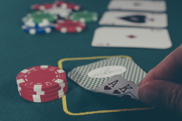 To represent casino games we included a picture of a poker game with someone's hand peeking at the cards.