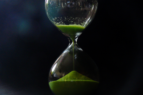 A picture of an egg time with green sand in it and against a black background - it looks mysterious, just like time.