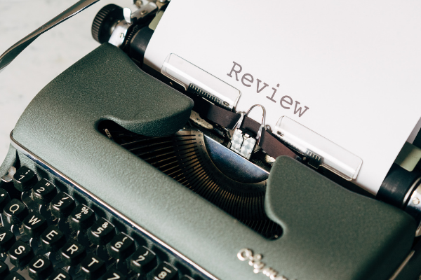 """A picture of a typewriter with the word """"review"""" printed on the paper that's coming out of it."""