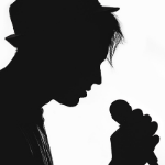 A silhouette of a man singing - looks a bit indie with a fedora