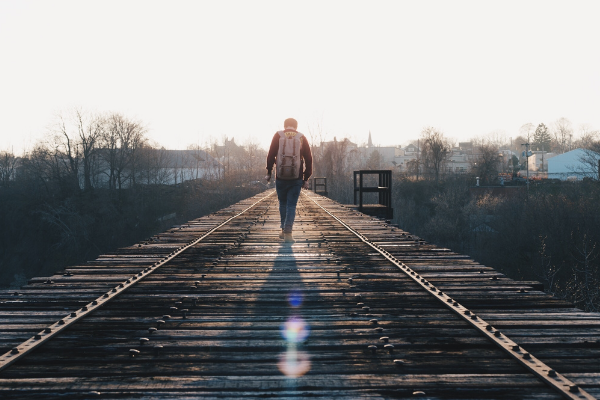 A picture of a man walking down a old wooden structure that sort of looks like an old railway track.