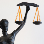 A picture of an ebony statue of a lady wearing a blindfold and holding up the scales of justice. It's to represent that this blog is about the law.