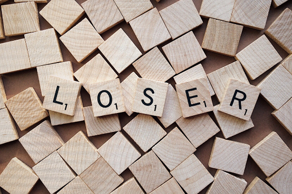 "A picture of lots of wooden squares with letters on 5 of them that spell ""loser"""