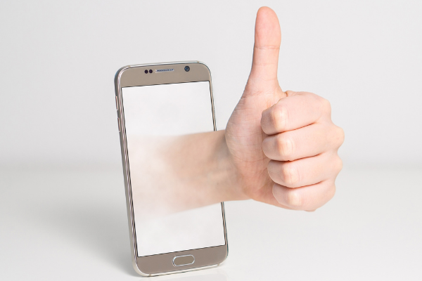 A picture of a hand with a thumbs up coming out of a mobile phone