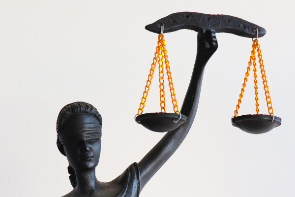 A picture of a statue of an exotic lady with a blind fold on holding up the scales of justice. The statue is made of something black, like ebony, with the chains of the scales being gold.. I've used this image to represent the law.