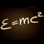 """An image that says """"E=MC2"""" to represent science. It's written in a blurry font that's white and looks a bit fuzzy, so it's an arty rendering of e = m c squared."""