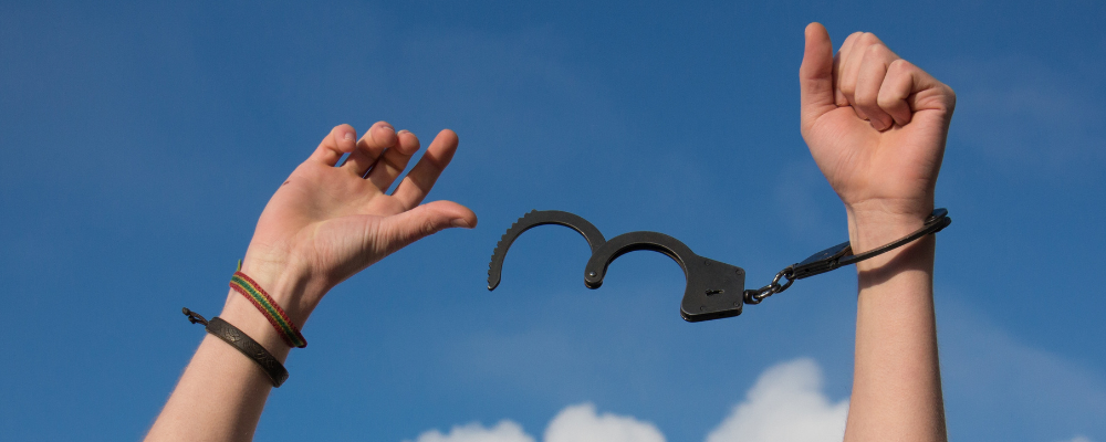 A picture of someone holding their arms up in the air with handcuffs that are about to come off. You can only see their arms and hands. The handcuffs are open and about to fall off. It's against a blue sky. It represents breaking free from addiction.