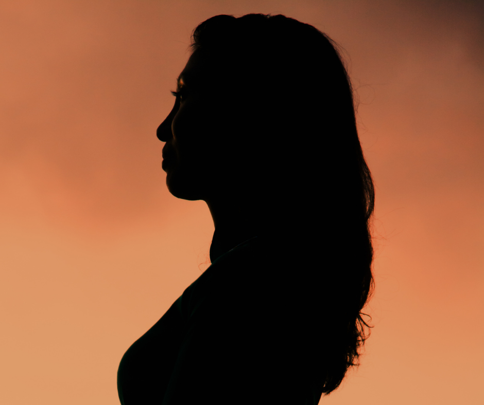 A woman in silhouette against an orange dusky background