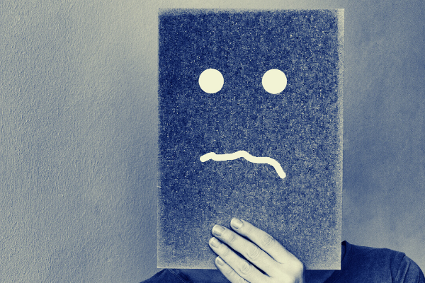 Foto seseorang yang memegang selembar karton di atas wajah dengan semprotan wajah sedih yang dilukis di atasnya.